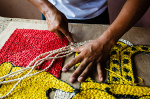 Craftsman making a sisal rope tapestry by hand for a rug or wall hanging.